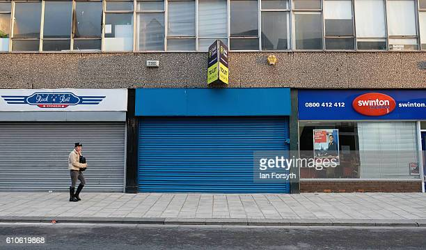A woman walks past shop fronts in Redcar high street on September 27 2016 in Redcar United Kingdom One year on since the SSI steel making plant at...