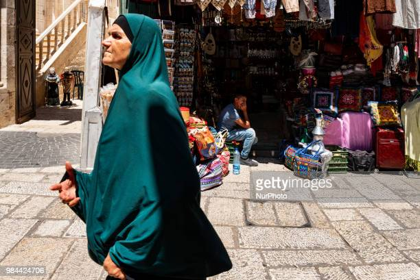 A woman walks past shops in the Muslim Quarter of the Old City of Jerusalem Israel on June 25 2018