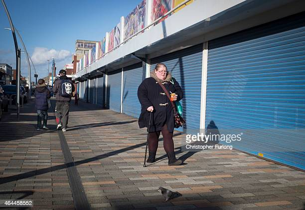 A woman walks past shuttered shops in Grimsby Greater Grimsby is famed for it's fishing and sea industries and is destined to be one of the key...
