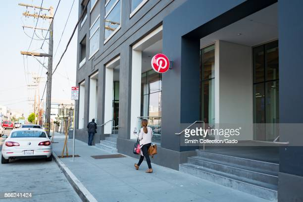 A woman walks past sign at the headquarters of social network Pinterest in the South of Market neighborhood of San Francisco California October 13...