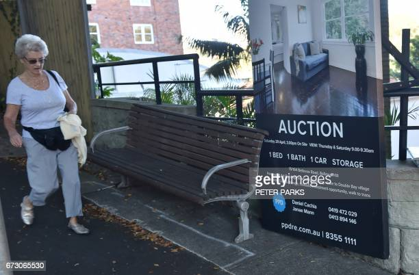 A woman walks past signage for a residential property auction in Sydney on April 26 2017 Australians are racking up extreme levels of debt to buy...