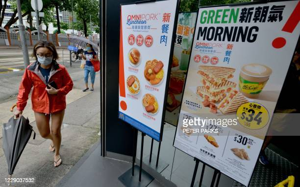 Woman walks past signs advertising new plant-based vegan-friendly meatless dishes at a McDonald's fastfood restaurant in Hong Kong on October 13,...