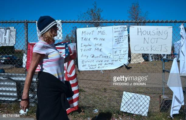 A woman walks past signs posted at the homeless encampment beside the Santa Ana River in Anaheim California on February 20 2018 Officials in Orange...