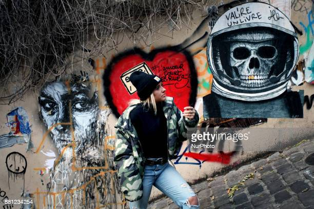 A woman walks past some graffities in Paris France on November 26 2017