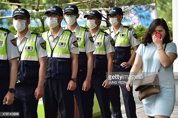 A woman walks past South Korean policemen wearing face masks in Seoul on June 23 2015 South Korea on June 23 reported three new MERS cases but no...