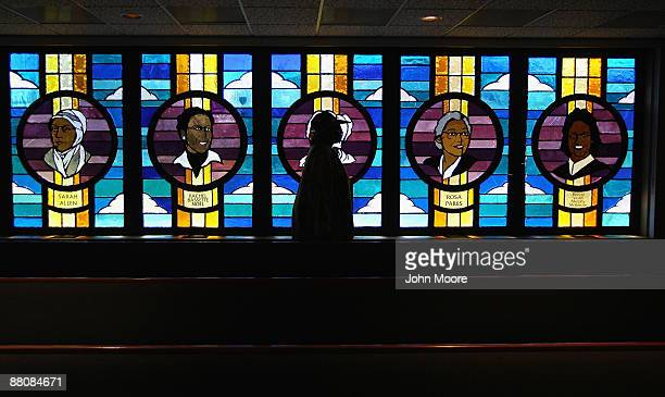 A woman walks past stained glass windows depicting historical African American women leaders after a Sunday church service on May 31 2009 in Denver...