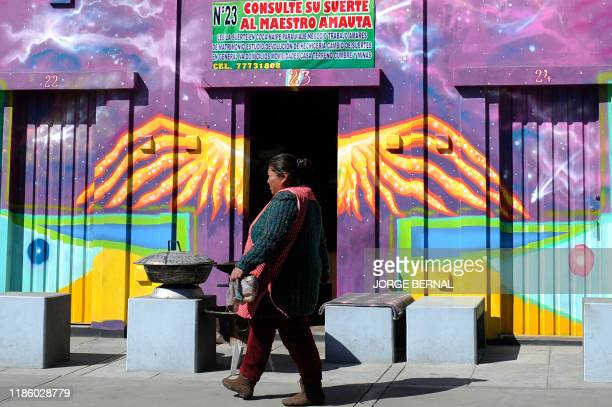 """Woman walks past stalls used by Yatiris to perform rituals in El Alto, on December 1, 2019. - Many Bolivians celebrate that the Bible is """"finally""""..."""