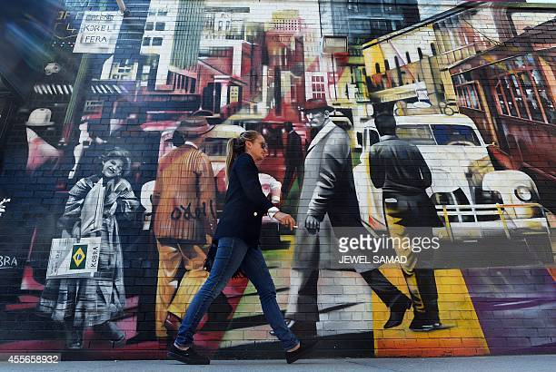A woman walks past street art depicting Manhattan city life in New York on September 18 2014 The US economy pumped out far fewer jobs than expected...