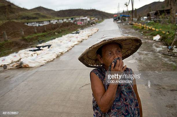A woman walks past super typhoon Haiyan victim bodybags awaiting burial in a massgrave at a cemetery in Tacloban on November 23 2013 The number of...