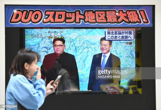 A woman walks past television footage of South Korean President Moon Jaein meeting North Korean leader Kim Jong Un in Tokyo on April 27 2018 North...