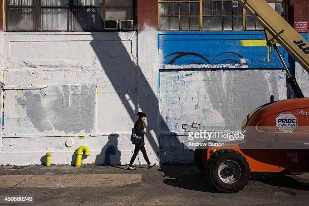 A woman walks past the 5 Pointz building which was painted over by developers in the dead of night after two decades serving as the mecca for...
