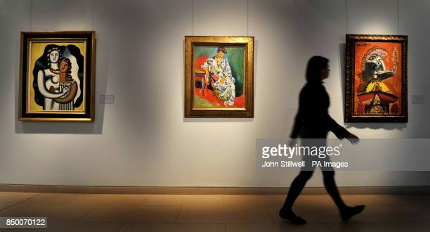 A woman walks past the Andre Derain painting of Madame Matisse au Kimono painted in 1905 which hangs with a painting by Picasso titled Buste d'homme...