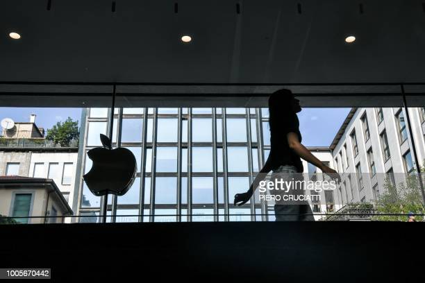 A woman walks past the Apple logo at the new Apple Store Liberty the first Italian flagship store of Apple in Milan on July 26 2018