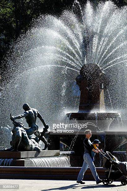 A woman walks past the Archibald Fountain in Sydney's Hyde Park 20 May 2004 New figures released 19 May by the Australian Bureau of Statistics show...