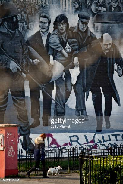 A woman walks past the 'Bloody Sunday' mural in the Bogside ahead of the Funeral of Martin McGuinness on March 22 2017 in Belfast Northern Ireland...