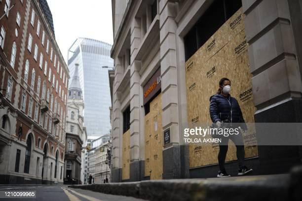 A woman walks past the boarded up shopfront of a Sainsbury's shop in the neardeserted City of london on April 16 during the novel coronavirus Covid19...
