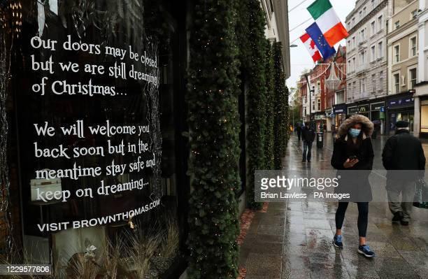 Woman walks past the Brown Thomas Christmas window on Dublin's Grafton street.
