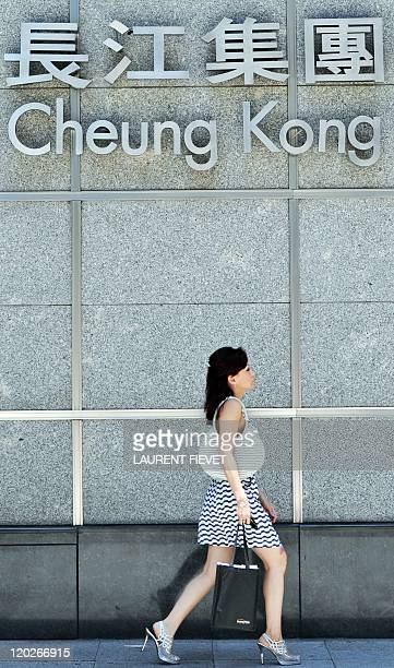 A woman walks past the Cheung Kong Center the headquarters of Cheung Kong Infrastructure Holdings in Hong Kong on August 3 2011 Shares in a firm...