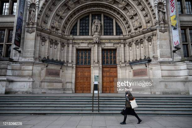 Woman walks past the closed doors of the V&A museum on March 18, 2020 in London, England. Wales and Scotland have today announced that all schools...