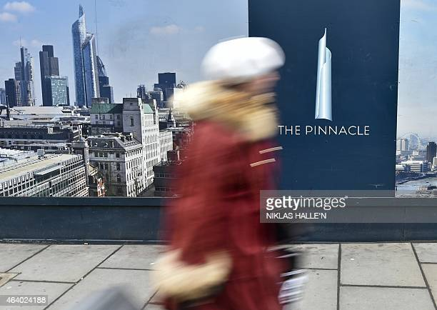 A woman walks past the construction site of the partially built 'The Pinnalce' skyscraper in Bishopsgate London on February 22 2015 French real...