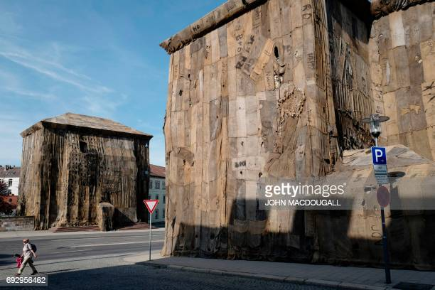 A woman walks past the early 19th century Torwache buildings covered in jute bags by Ghanian artist Ibrahim Mahama during the Documenta 14 art...