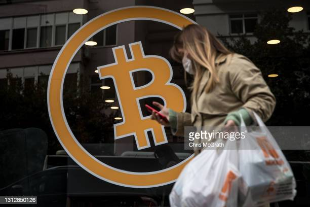 Woman walks past the entrance of a cryptocurrency exchange office on April 16, 2021 in Istanbul, Turkey. Turkey's Central Bank announced a ban on the...