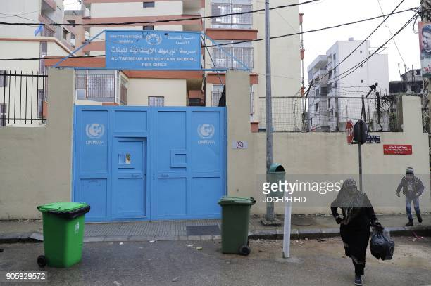 A woman walks past the entrance of a school for Palestinian refugees funded by the UNRWA agency at the Burj alBarajneh camp in the Lebanese capital...