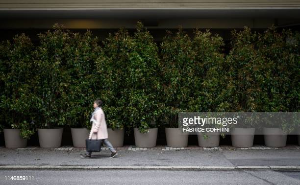 Woman walks past the entrance of The Fairmont Le Montreux Palace hotel hidden by plants in Montreux on May 29 which is scheduled to host the annual...