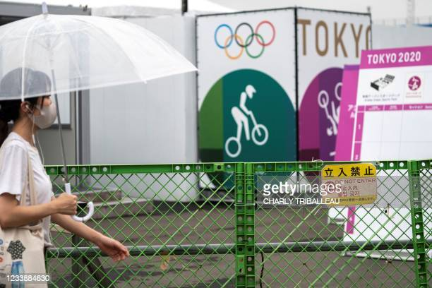 Woman walks past the entrance to the Ariake Urban Sports Park, the main venue for cycling BMX freestyle, cycling BMX racing and skateboarding events...