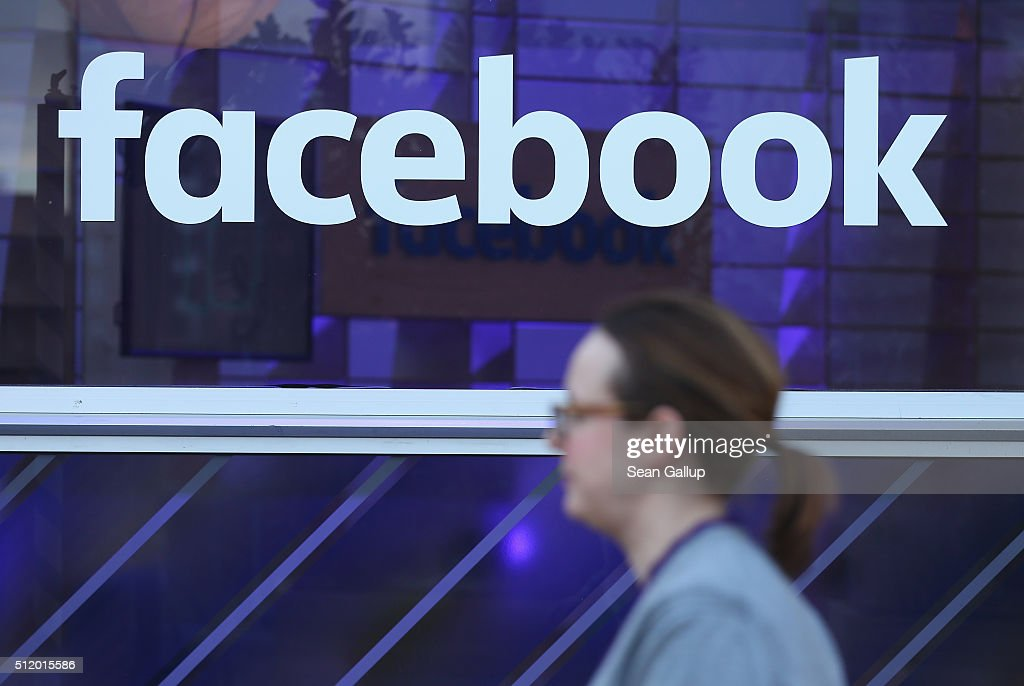 A woman walks past the Facebook logo at the Facebook Innovation Hub on February 24, 2016 in Berlin, Germany. The Facebook Innovation Hub is a temporary exhibition space where the company is showcasing some of its newest technologies and projects.