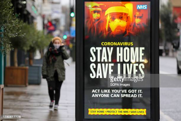 Woman walks past the Government's 'Stay Home, Save Lives' Covid-19 publicity campaign poster in London, as the number of cases of the mutated variant...