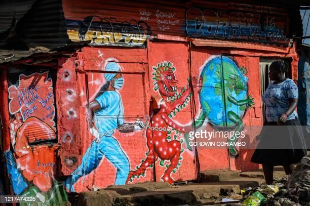Woman walks past the graffiti mural related to the COVID-19 coronavirus painted by the residential art group, art360, at the Kibera slum in Nairobi...