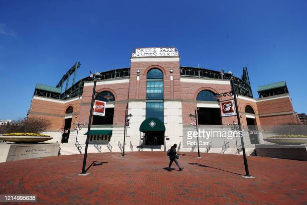 Woman walks past the home plate entrance of Oriole Park at Camden Yards on March 26, 2020 in Baltimore, Maryland. The Baltimore Orioles and New York...