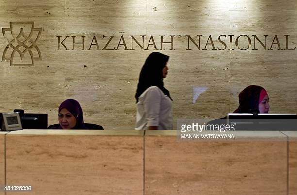 A woman walks past the Khazanah Nasional Berhad logo at the front desk of the Khazana Nasional office in Kuala Lumpur on August 29 2014 Malaysia...