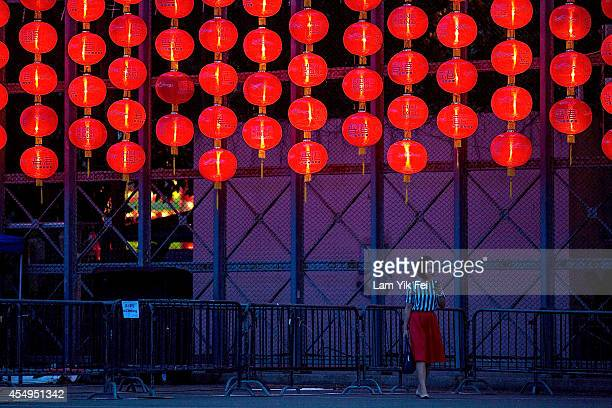 A woman walks past the lantern during lantern festival as part of the MidAutumn Festival at Victoria Park in Hong Kong on September 8 2014 in Hong...