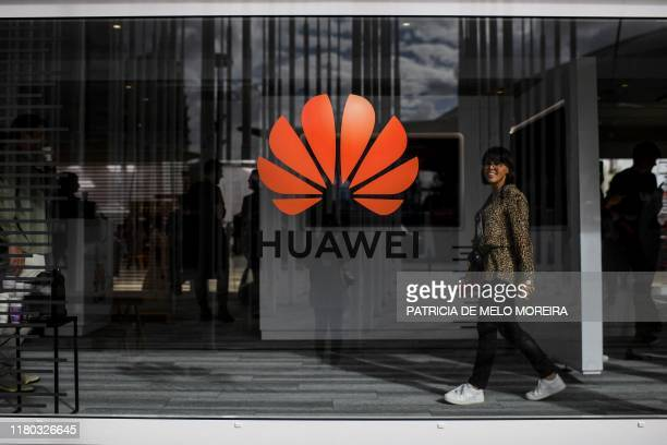 A woman walks past the logo of Chinese telecom giant Huawei during the Web Summit in Lisbon on November 6 2019 Europe's largest tech event Web Summit...