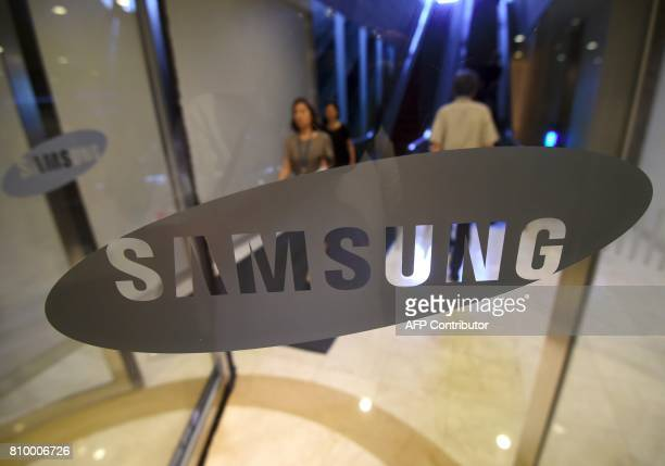 A woman walks past the logo of Samsung at the company's showroom in Seoul on July 7 2017 Samsung Electronics expects profits to soar 72 percent in...