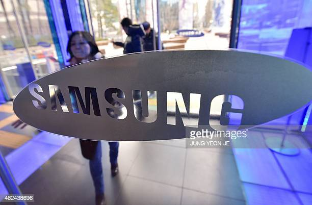A woman walks past the logo of Samsung Electronics at its showroom in Seoul on January 29 2015 Samsung Electronics the world's largest smartphone...
