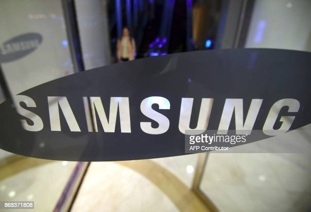 A woman walks past the logo of Samsung Electronics at the company's showroom in Seoul on October 31 2017 South Korean tech giant Samsung Electronics...