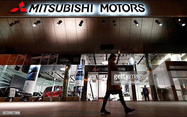 A woman walks past the Mitsubishi Motors headquarters on April 20 2016 in Tokyo Japan Mitsubishi Motors share plunged more than 15% after the...