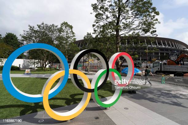 A woman walks past the Olympic rings displayed in front of the New National Stadium the main venue for the Tokyo 2020 Olympic and Paralympic Games...