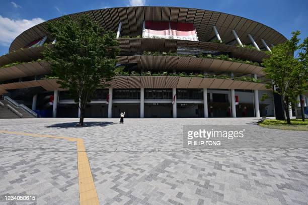 Woman walks past the Olympic Stadium, main venue of the Tokyo 2020 Olympic Games in Tokyo on July 19, 2021.
