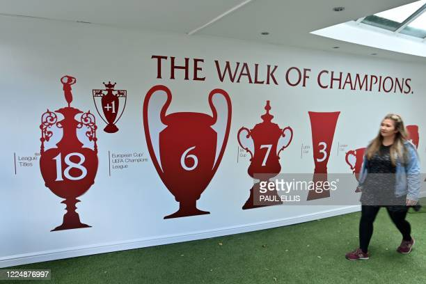 A woman walks past the recently updated Wall of Champions reflecting Liverpool's trophy wins in Hotel Anfield ahead of the English Premier League...