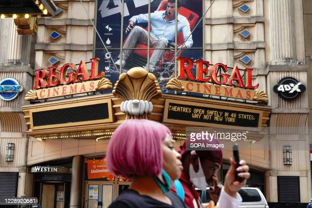 Woman walks past the Regal Cinemas. Regal Cinemas which is the second-largest operator of theatres in the United States, plans to close all 500 US...