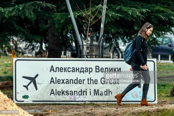 A woman walks past the removed sign for the airport Alexander the Great in Skopje on February 19 2018 The Macedonian Government took the decision to...