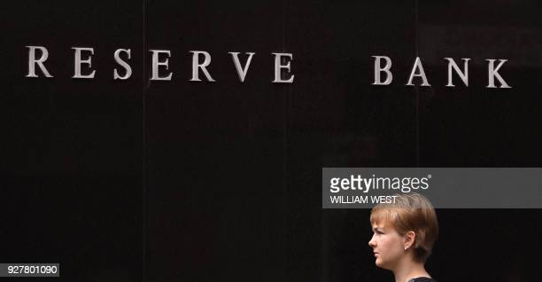 A woman walks past the Reserve Bank of Australia building in Sydney on March 6 as Australia's central bank kept interest rates at a record in a...