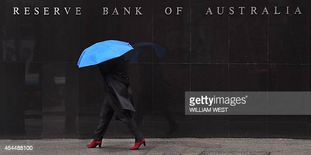 A woman walks past the Reserve Bank of Australia sign in Sydney on September 2 as Australia's central bank kept interest rates on hold at a record...
