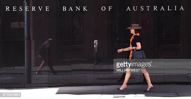 A woman walks past the Reserve Bank of Australia sign in Sydney on October 4 as Australia's central bank kept interest rates at a recordlow in the...