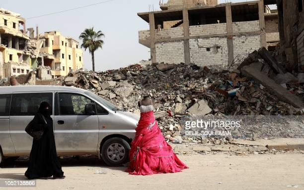 Woman walks past the rubble of a building in the northern Syrian city of Raqa on October 14, 2018. - Once the de facto Syrian capital of the Islamic...