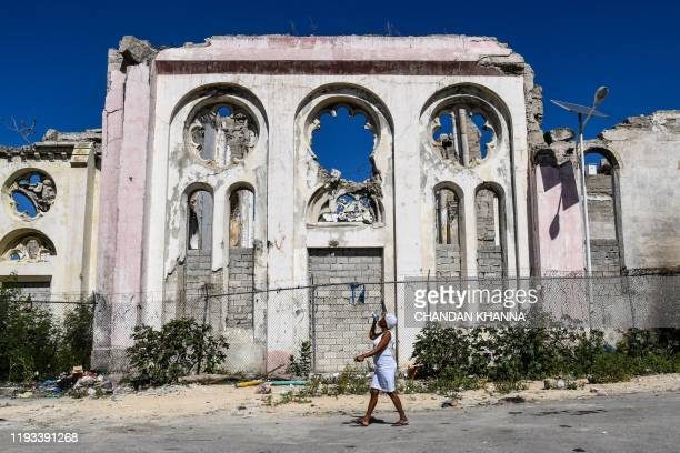 Woman walks past the ruins of Notre Dame Cathedral during Haiti's 10th earthquake anniversary in Port-au-Prince, on January 12, 2020. - Haitians on...